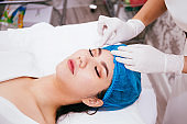 Beautiful young Asian woman getting her face cleansed by beautician at cosmetology beauty clinic.