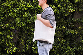 Young male hipster holding and carrying an empty blank canvas tote bag over green nature background - with copy space.