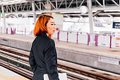 Young beautiful Asian businesswoman holding a laptop and waiting for the train to arrive.
