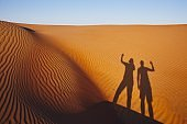 Shadows of two friends on sand dune