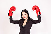 Young Asian business woman wearing boxing gloves in white isolated background - business winning and victory concept.