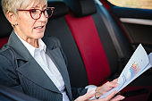 Serious mature businesswoman preparing for a meeting while riding in a car, looking at sales charts and documents