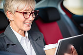 Happy mature businesswoman working on a tablet while commuting to meeting. Sitting on a back seat of a car and holding a cup of coffee