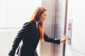 Young Asian businesswoman in hurry rush hour pressing an elevator button.