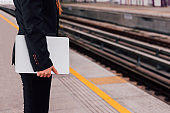 Close up of businesswoman holding a laptop and waiting for the train to arrive.