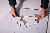 Hands of business man working on finishing last missing pieces of jigsaw on the white desk - critical thinking and problem solving business concept.