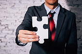 Business man giving the missing piece of jigsaw as offering a success, business solution in corporate partnership.