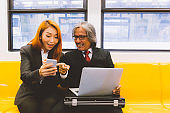 Portrait of two Asian businesspeople discussing and and working on the go on train.