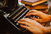 Human hands typing on vintage type writer machine and piles of books on wooden table - very selective focus.
