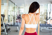 Close up of young muscular and active Asian female sportswoman having shoulder strain during indoors workout gym