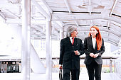 Asian Businesswoman and businessman walking and talking on the go in urban city outdoor scene.