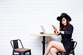 Young fashionable Asian business woman looking at watch, waiting for someone with a mobile phone and laptop. Late for appointment concept
