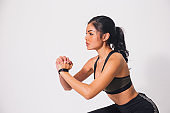 Young sporty muscular woman doing squats isolated over white background. Woman in sport clothing performing exercise
