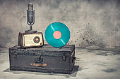 Retro radio from 60s, studio microphone from 50s, and blue vinyl disc record circa 70s on old aged classic travel trunk with leather handles. Vintage style filtered photo