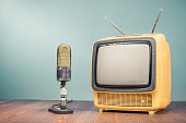Retro old outdated yellow TV receiver from circa 70s and studio microphone on wooden table front mint green wall background. Vintage style filtered photo