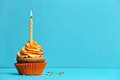Birthday cupcake with candle on color background