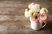 Vase with beautiful ranunculus flowers on wooden table