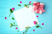 Sheet of paper, roses and gift box on wooden background