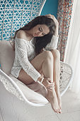 Young attractive woman chilling at home in comfortable hanging chair. Natural beauty of sensual brunette girl relax in living room.