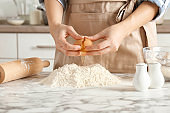 Woman breaking egg over pile of flour on table in kitchen