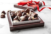 Box with different tasty chocolate candies on table
