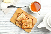 Board with toasted bread and cup of tea on wooden background, top view