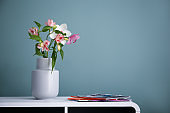Vase with beautiful flowers on table against color background. Interior decor element