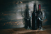 bottles with red wine and wine glasses on a wooden surface