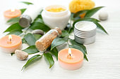 Beautiful composition with spa cosmetics and candles on light background