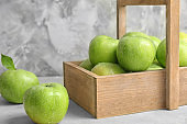 Wooden basket with fresh green apples on table