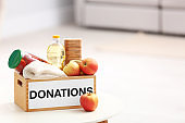 Donation box with food products on table indoors