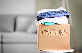 Donation box with clothes on table indoors