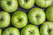 Fresh green apples with water drops on table, top view