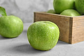 Fresh green apple with water drops on table