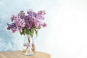 Vase with beautiful blossoming lilac on table against light background. Spring flowers