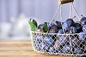 Basket with tasty fresh plums on wooden table