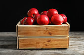 Wooden crate with fresh red apples on table against black background