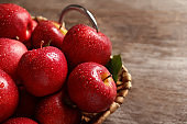 Basket with fresh ripe red apples on wooden table, closeup