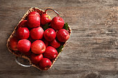 Basket with fresh ripe red apples on wooden background