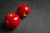 Ripe red apples on grey background