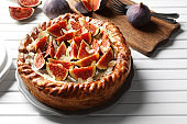 Fresh cake with figs on wooden background