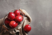 Basket with fresh ripe red apples on grey background