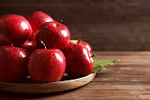 Plate with fresh ripe red apples on wooden table
