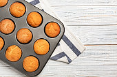 Baking tray with tasty cupcakes on table. Fresh from oven