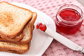 Plate with toasted bread and jam on table