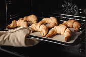 Person taking baking sheet with croissants from oven, closeup