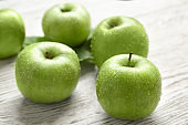 Fresh green apples on wooden background