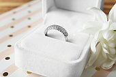 Box with luxury engagement ring on table, closeup