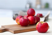 Ripe red apples on wooden board