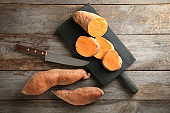 Sweet potatoes with slices on wooden table